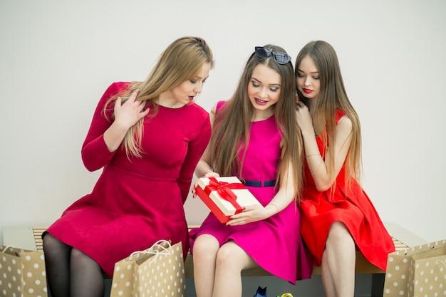 Mulheres felizes e animadas, ela recebeu uma encomenda postal e está desembalando seu presente