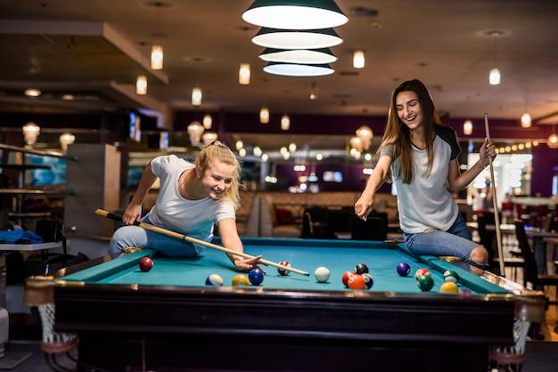 Mulheres felizes e animadas jogando bilhar juntas