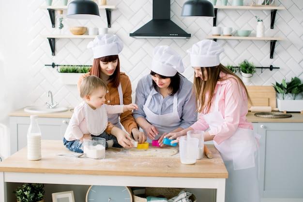 Mulheres felizes em aventais brancos cozendo juntos, cortando formas de massa de biscoito de açúcar com cortadores de biscoito. garotinha ajuda a fazer biscoitos junto com a mãe, tia e avó