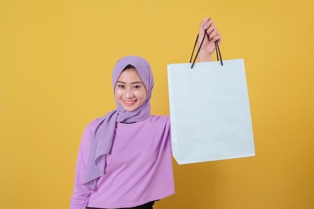 Mulheres felizes em compras, mostrando bolsas, vestindo uma camiseta roxa, conceito de compra