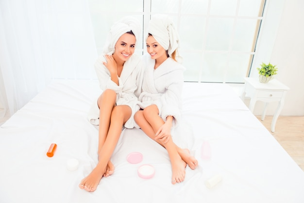 Mulheres felizes em roupões de banho sentadas na cama com pote de creme e loção