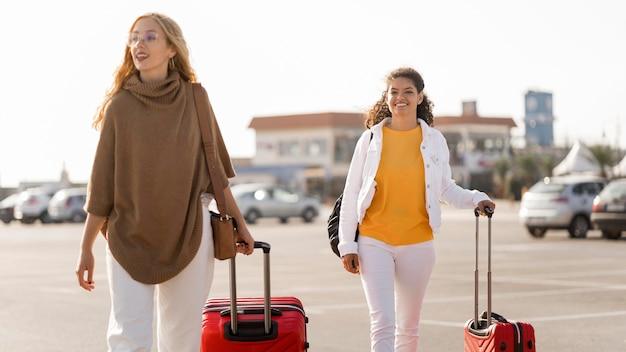 Mulheres felizes em tiro médio carregando bagagem