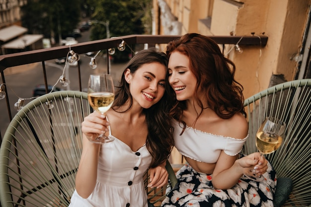 Mulheres felizes em trajes elegantes degustam vinho branco