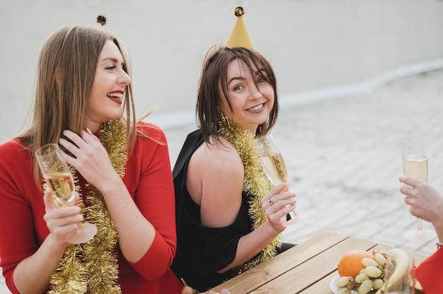 Mulheres felizes em vestidos vermelhos e pretos, festejando no telhado