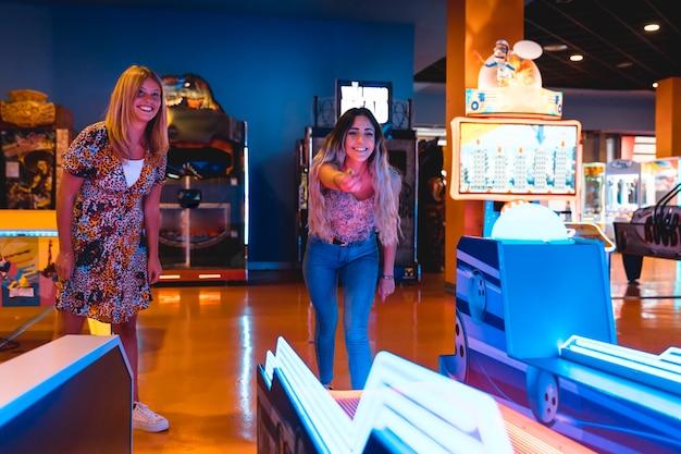 Mulheres felizes jogando jogo de arcade