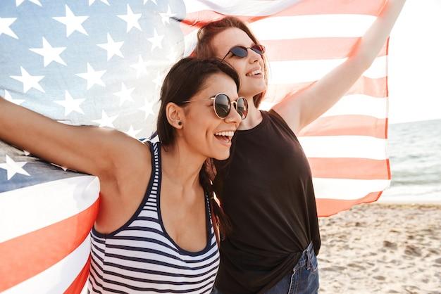 Mulheres felizes na praia segurando a bandeira dos eua e se divertindo ao ar livre