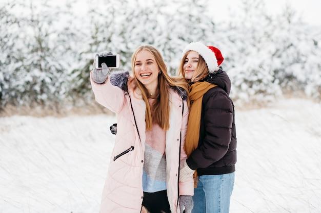Mulheres felizes no chapéu de papai noel tomando selfie na floresta de inverno