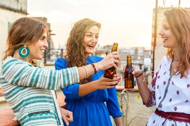 Mulheres felizes que apreciam uma cerveja em um telhado em barcelona