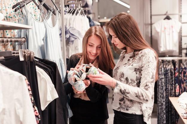 Mulheres felizes que compram sapatas em uma loja.