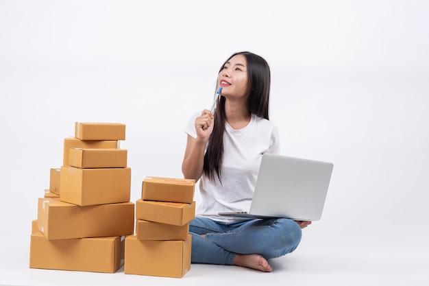 Mulheres felizes que estão pensando no branco blackground online operadores de negócios de compras independente