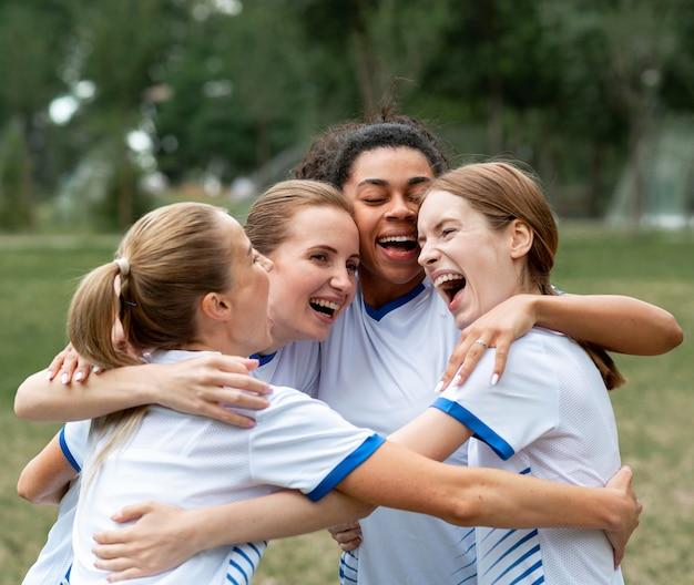 Mulheres felizes se abraçando ao ar livre
