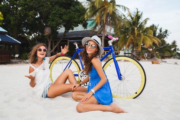 Mulheres felizes se divertindo em uma praia tropical, mulheres viajando de férias na tailândia com bicicletas