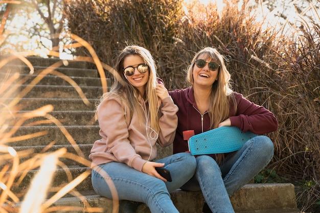 Mulheres felizes, sentado na luz do sol no banco