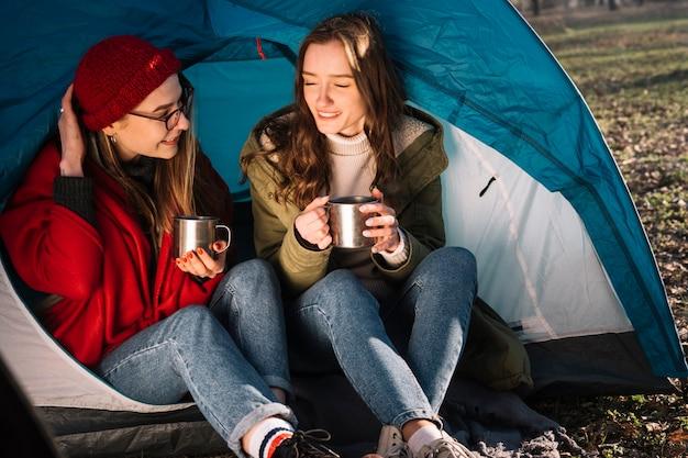Mulheres felizes, sentado na tenda