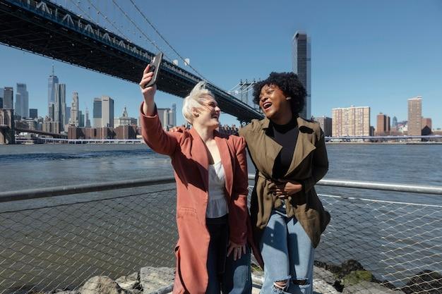 Mulheres felizes tirando selfie em foto média