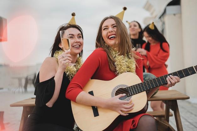 Mulheres felizes tocando violão