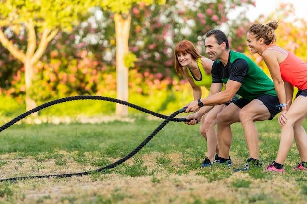 Mulheres felizes treinando no parque com seu personal trainer e usando uma corda de batalha.