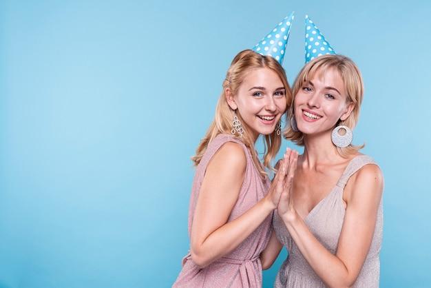 Mulheres felizes usando chapéus de festa
