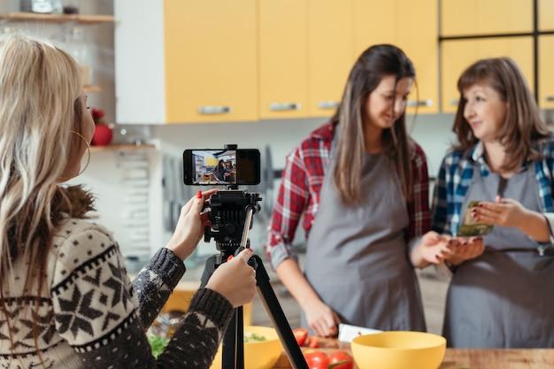Mulheres filmando processo de cozimento na câmera do telefone