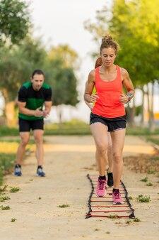 Mulheres fortes fazendo circuito de fitness no parque e malhando com seu personal trainer.