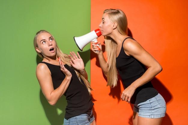 Mulheres gêmeas fazendo anúncio com megafone