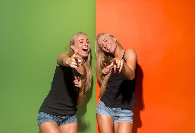 Mulheres gêmeas felizes apontam para você, retrato em close de meio comprimento