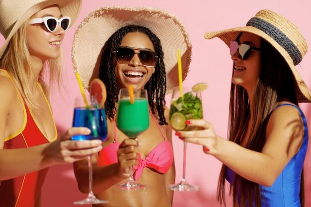 Mulheres glamorosas em trajes de banho e chapéus posam com coquetéis na cor rosa