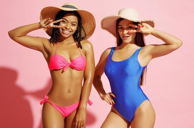 Mulheres glamourosas em trajes de banho e chapéus posam em rosa