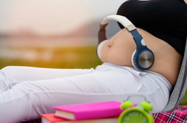 Mulheres grávidas abrem uma música no estômago na barriga para ouvir através do fone de ouvido
