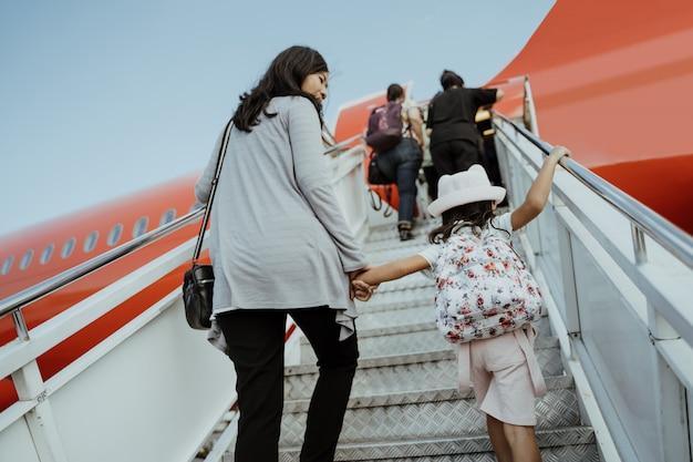 Mulheres grávidas asiáticas e suas filhas sobem as escadas do avião