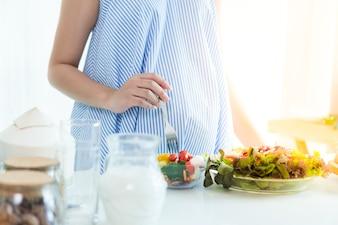 Mulheres grávidas Colocar em um vestido azul. Ela está comendo salada de café da manhã.