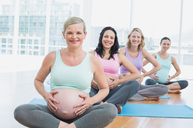 Mulheres grávidas em uma aula de ioga sentado em tapetes tocando seus choques