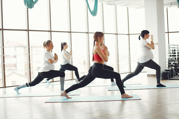 Mulheres grávidas fazendo yoga com um treinador