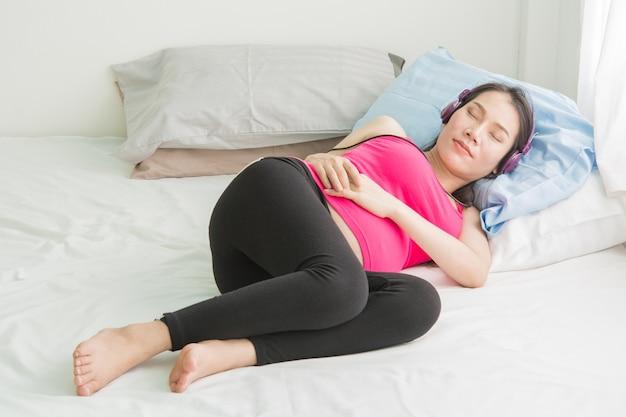 Mulheres grávidas ouvem música no telefone.