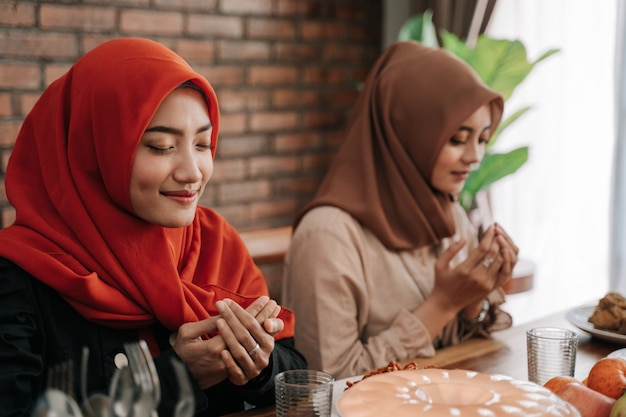 Mulheres hijab rezam juntas antes das refeições