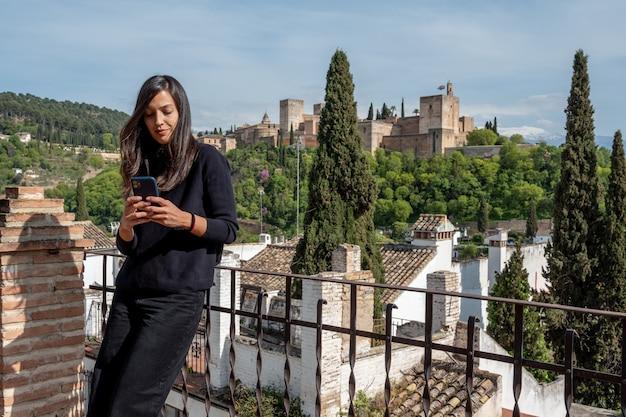 Mulheres hispânicas enviam mensagens para turistas em um telefone celular em um terraço com vista para a fortaleza de alhambra em granada, espanha