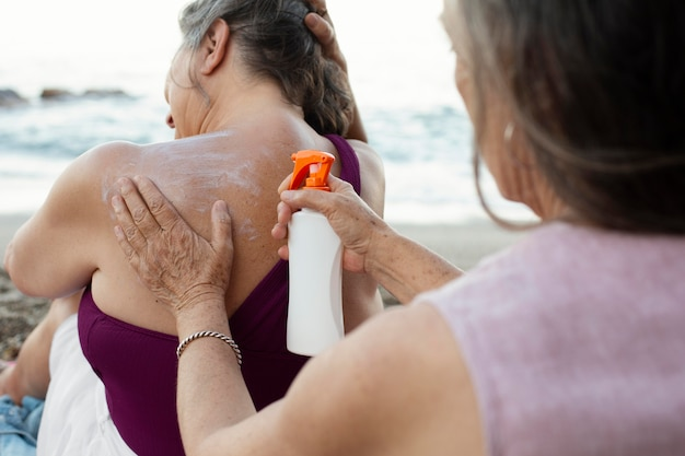 Mulheres idosas aplicando protetor solar na praia
