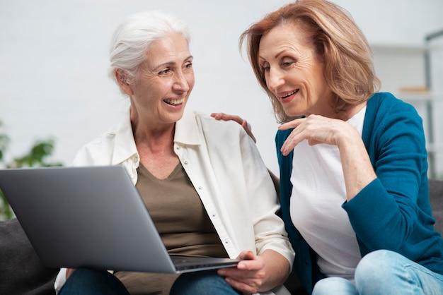 Mulheres idosas junto com um laptop