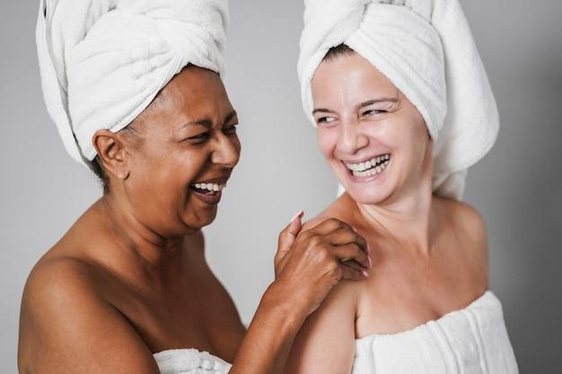 Mulheres idosas multirraciais com pele e corpo diversificados rindo juntos enquanto usam toalhas corporais - foco principal no rosto feminino africano