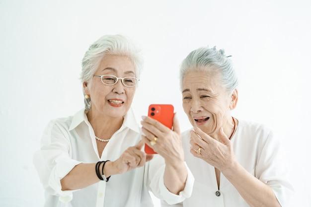 Mulheres idosas olhando para telas de smartphones com um sorriso