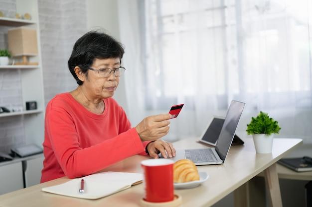 Mulheres idosas procurando cartão de crédito e usando laptop para fazer compras online