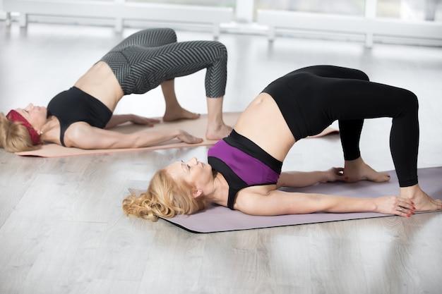Mulheres idosas que exercem exercícios de ombro