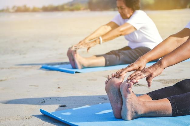 Mulheres idosas que exercitam na praia pelo mar ar fresco, corpo forte