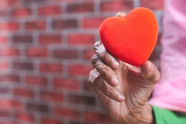 Mulheres idosas segurando coração vermelho close-up.