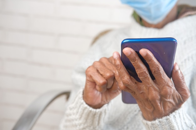 Mulheres idosas segurando máscara facial usando telefone inteligente close-up
