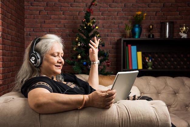 Mulheres indianas asiáticas sêniors ouvindo música usando fones de ouvido enquanto seguram um computador tablet ou usam ou falam no telefone e estão sentadas no sofá ou sofá em casa