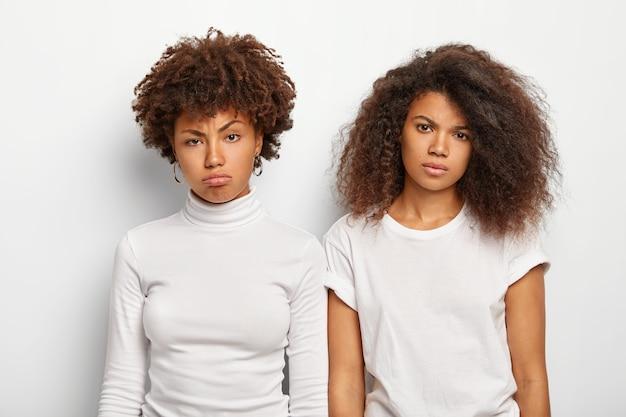 Mulheres infelizes e entediadas com cabelos cacheados, têm rostos desagradáveis