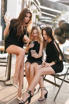 Mulheres interessadas em vestidos pretos com penteado moderno olhando para a tela do telefone, enquanto bebem champanhe