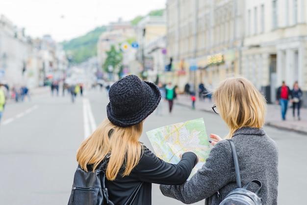 Mulheres irreconhecíveis navegando com o mapa