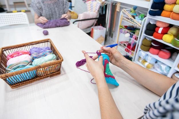 Mulheres irreconhecíveis praticando e aprendendo artes e ofícios de malha.